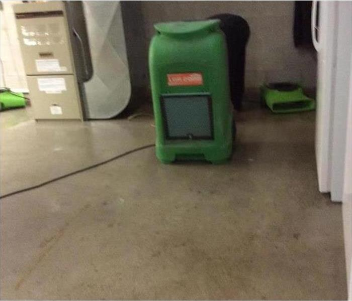 Commercial building concrete floor dry with SERVPRO green tools